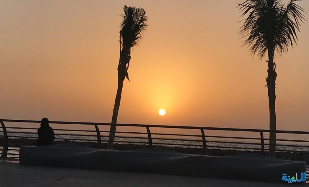 سيدة تراقب غروب الشمس على كورنيش جدة الجديد